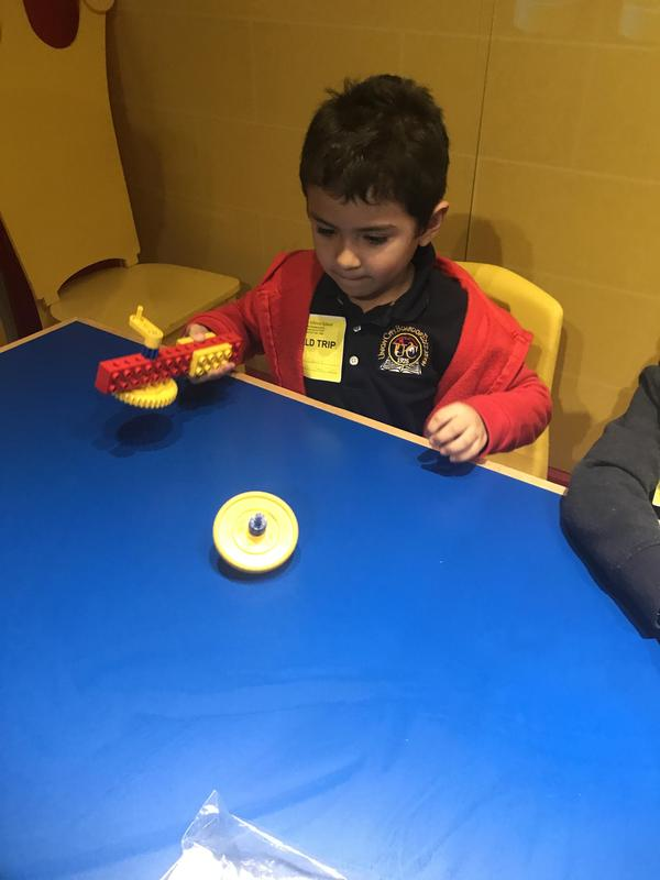 boy creating a spinner toy with gears
