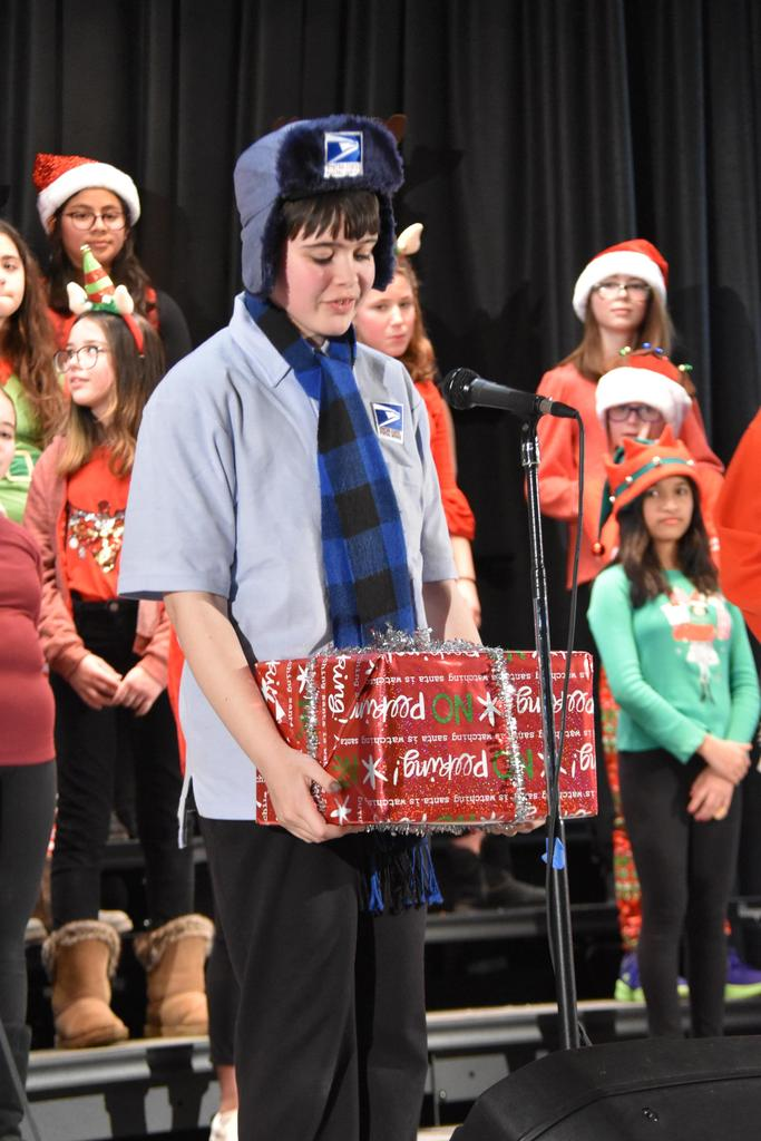 A boy dressed as a postal worker holds a wrapped present