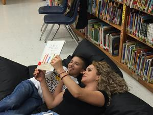 Mother and son reading a book together.