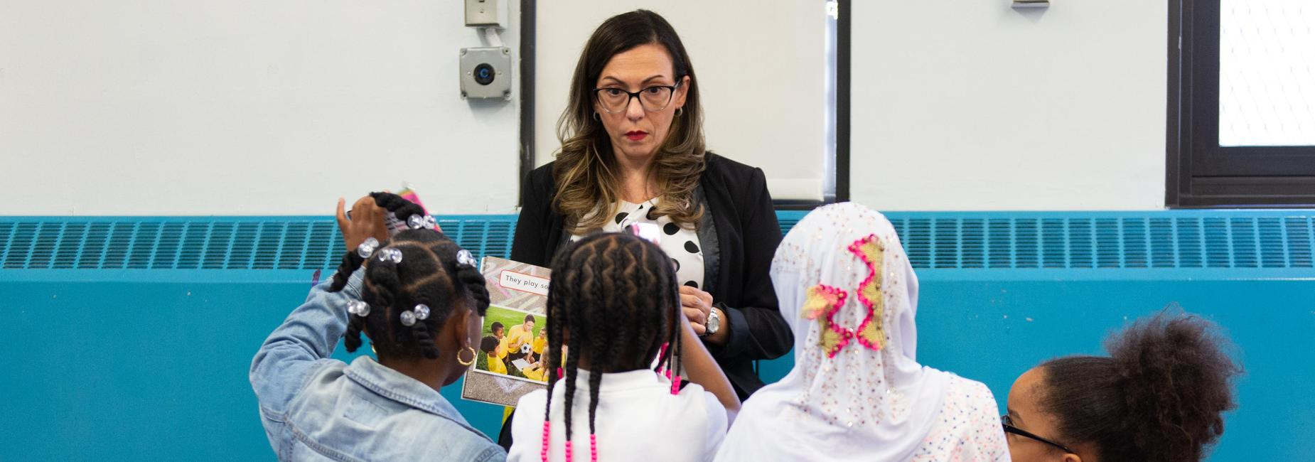 An elementary school teacher reading a book to four students.