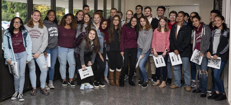 Group of NHS students pose in middle school lobby