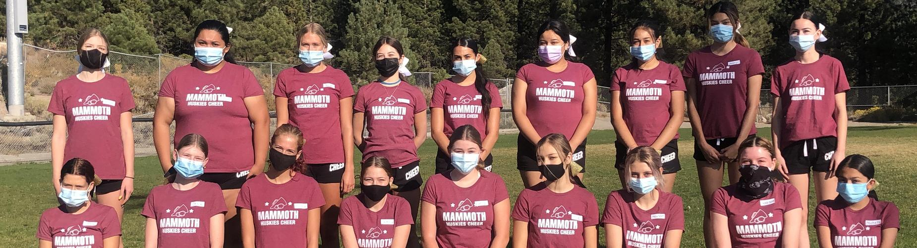 Mammoth High School cheer squad poses with back row standing front row kneeling. All girls wearing masks