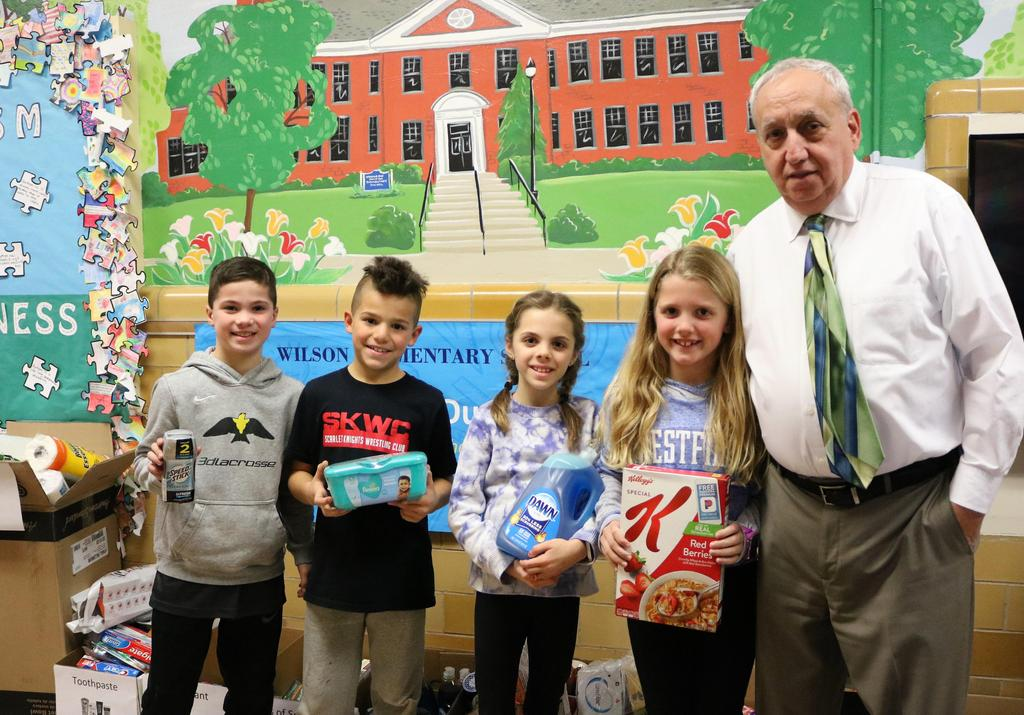 Photo of Wilson principal Joseph Malanga with four students holding donated non-perishable items during Month of Hope.