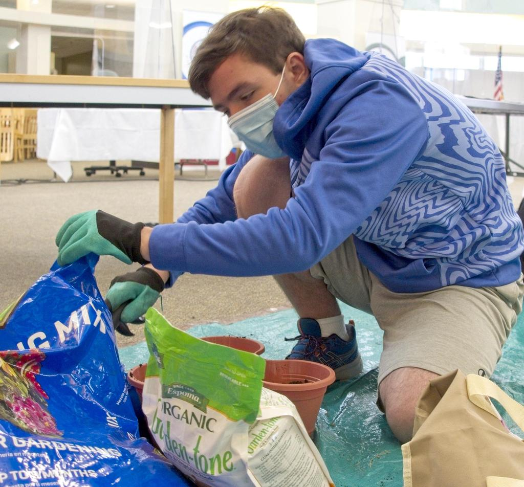 A student works with soil and gardening supplies