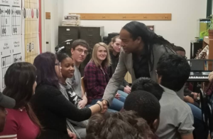 Bass player Doug Wimbish shakes hands with HSC students