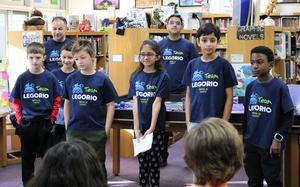 Team Legorio, a group of 6 fourth graders from Jefferson Elementary School, pose for a picture before demonstrating their robotic prowess before a gathering of their schoolmates as they outlined the challenges they faced during an international robotics competition.