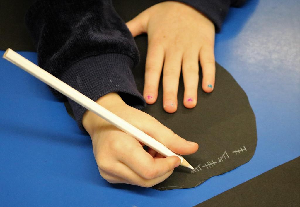 Photo of Tamaques student working on 100th Day activity.   Tight shot of hand with white color pencil.