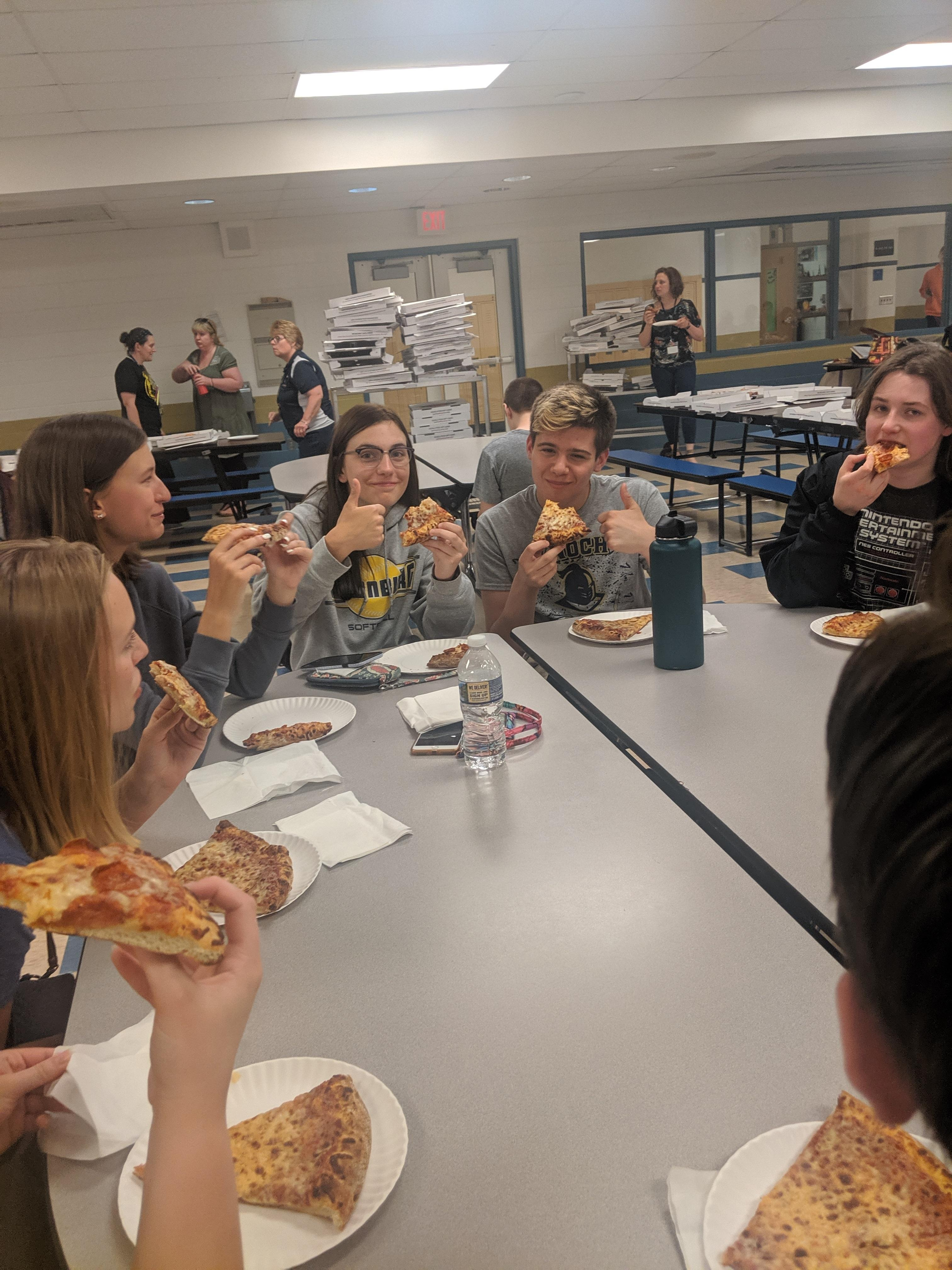 Students eating pizza.