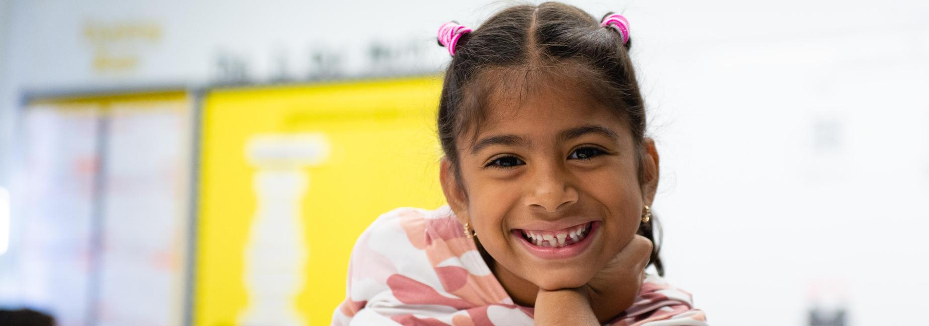 An elementary school student smiling at the camera.