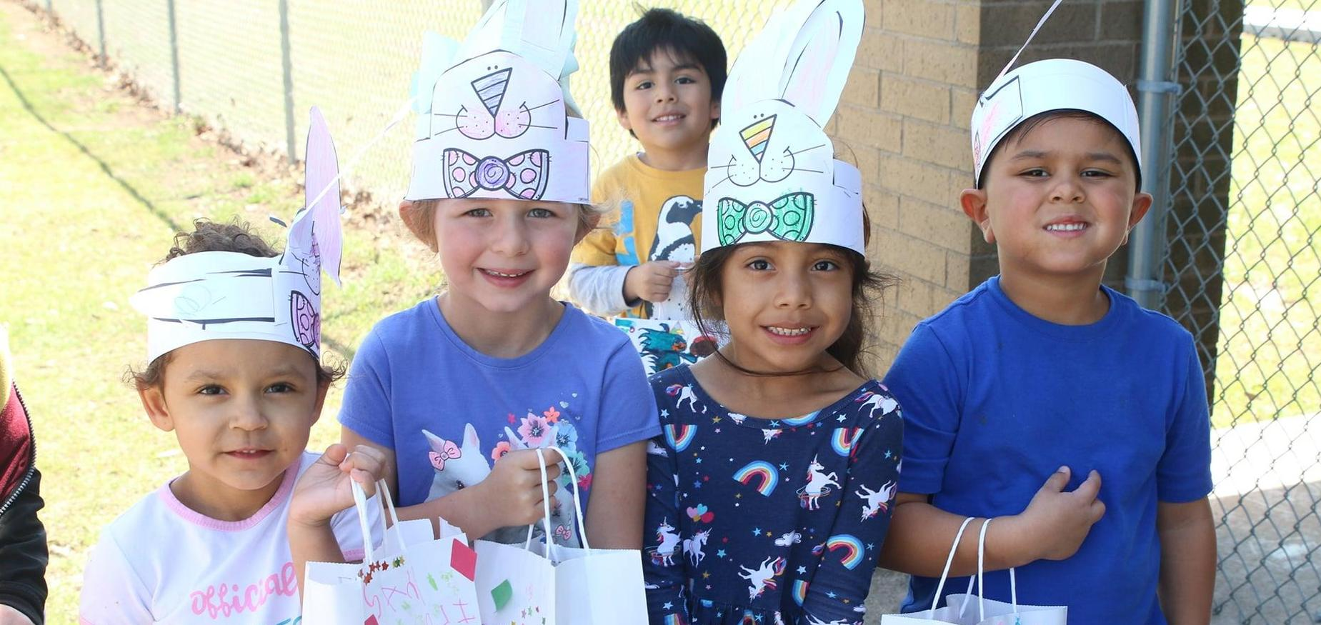 students smile with easter hats on