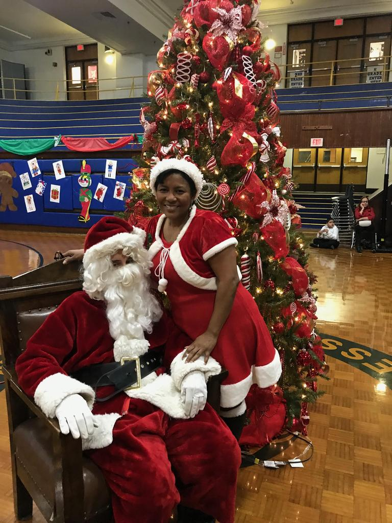 Santa and ms. vandorhorst clause by Christmas tree in the gym