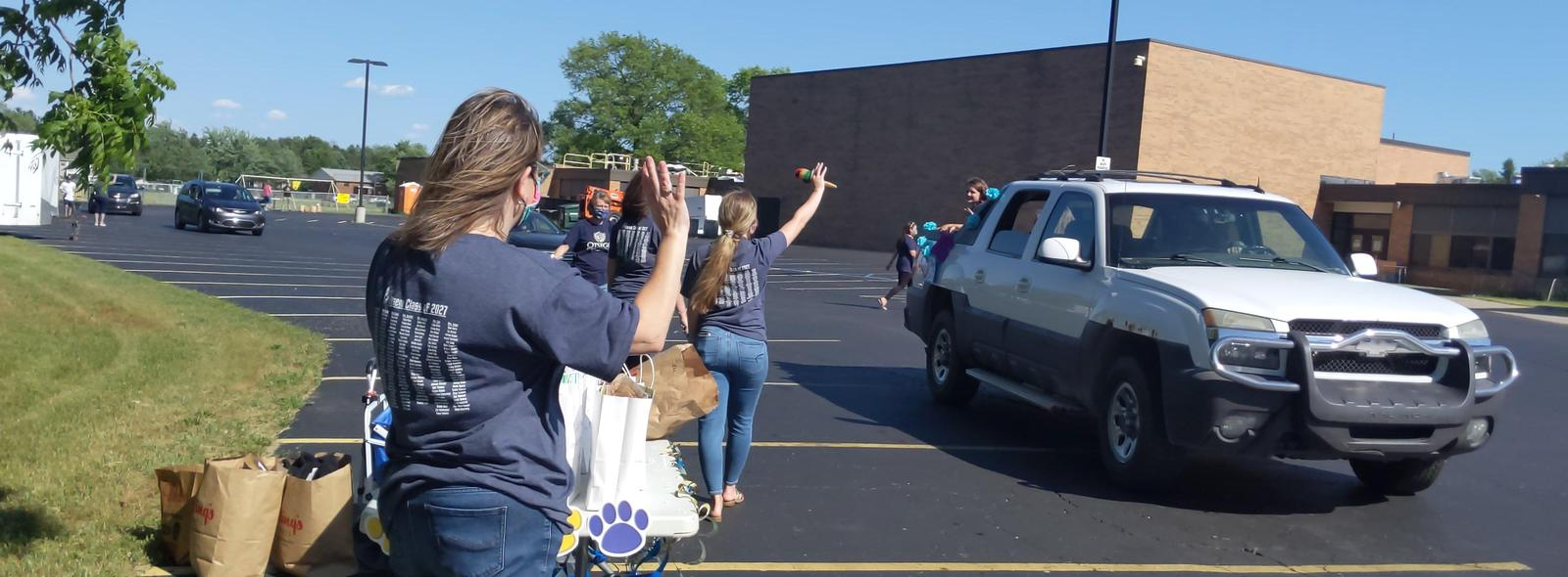 teachers wave goodbye at the end of the year parade