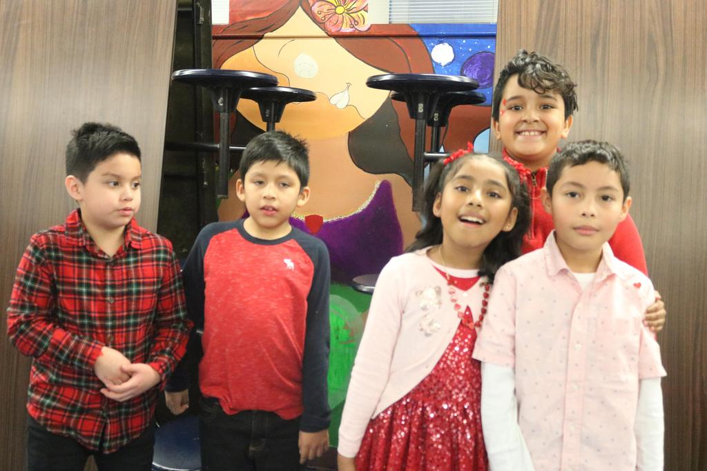 several kids wearing red and pink standing together
