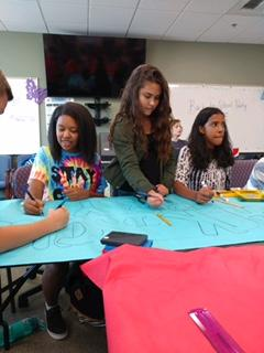 Picture of students making posters for the party