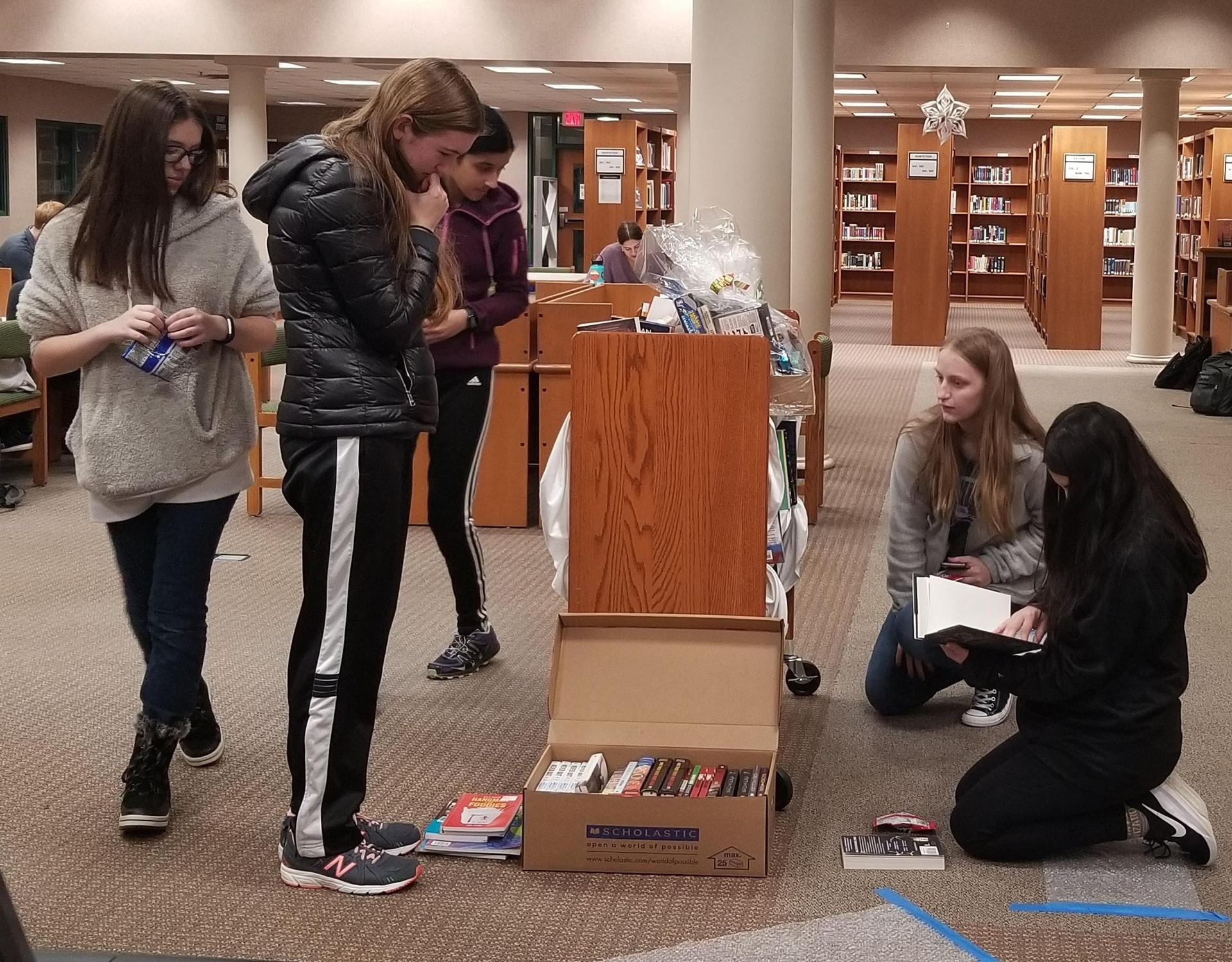 Several female students look at books on a metal cart