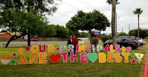 Principals standing next to yard sign.
