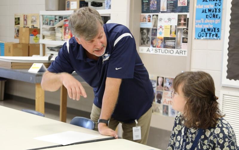A picture of art teacher Robert Urban with a student.