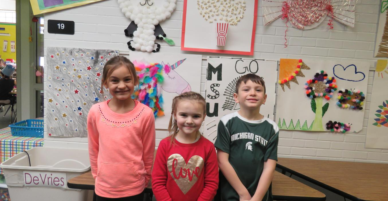 Students show their 100th day celebration posters.