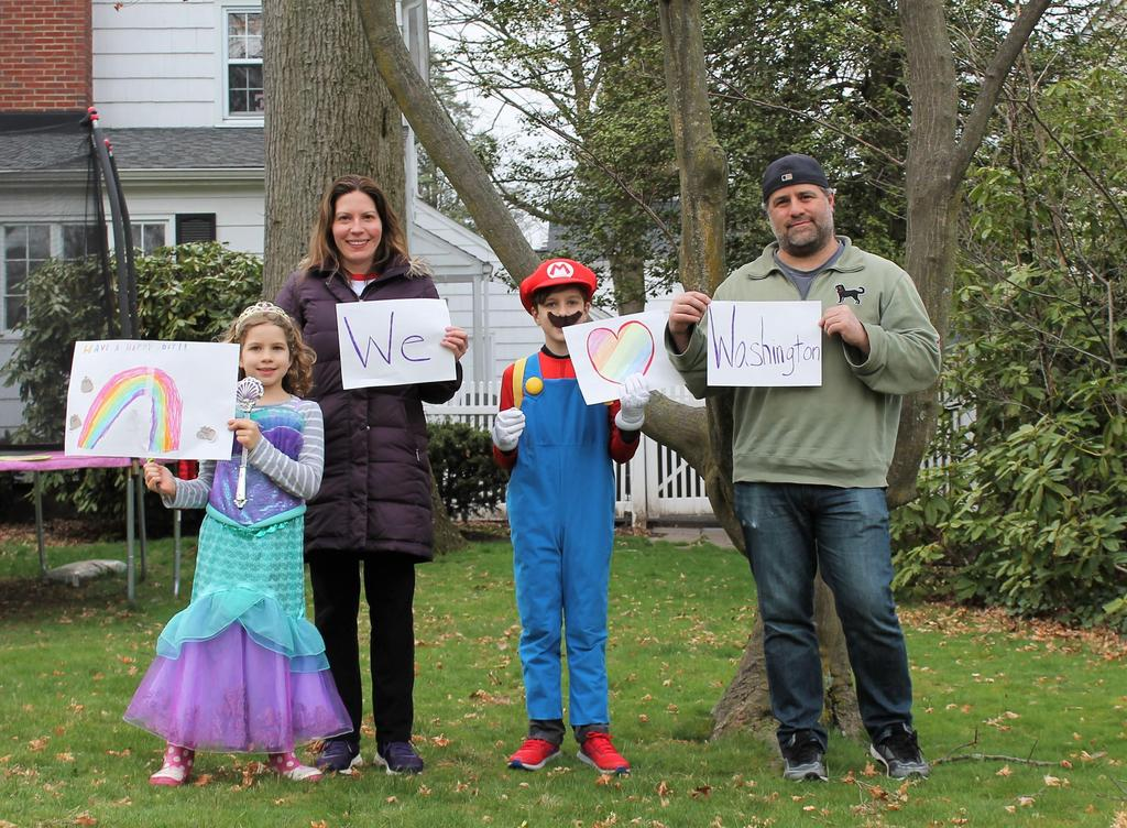 Photo of Washington family posing with signs for teachers during car parade for school community.