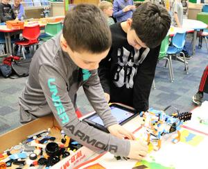 Two Wilson students working on a Lego robot they built and programmed during an afterschool STEAM session.