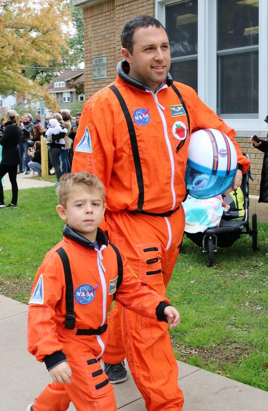Man and student sport matching astronaut costumes in Lincoln School Halloween Parade.