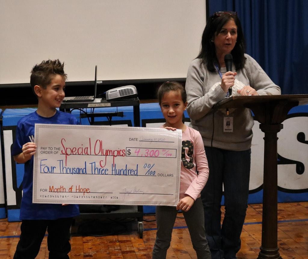 Photo of Wilson teacher and two students holding representative check indicating amount raised for the Special Olympics during Month of Hope.