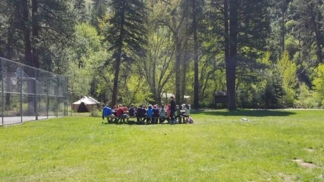 students sitting at picnic tables in large grass area of camp
