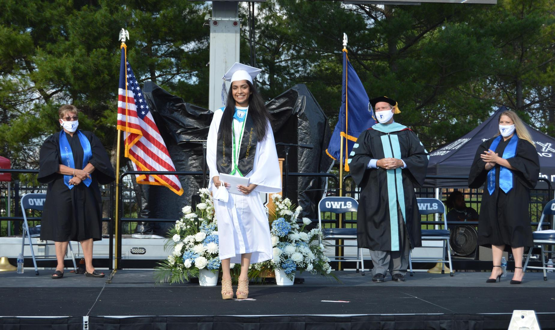 Multicultural club president wearing her black sash posed with her diploma dressed in her white cap and gown