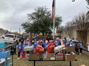 dyer students and business volunteers are surrounded by donations