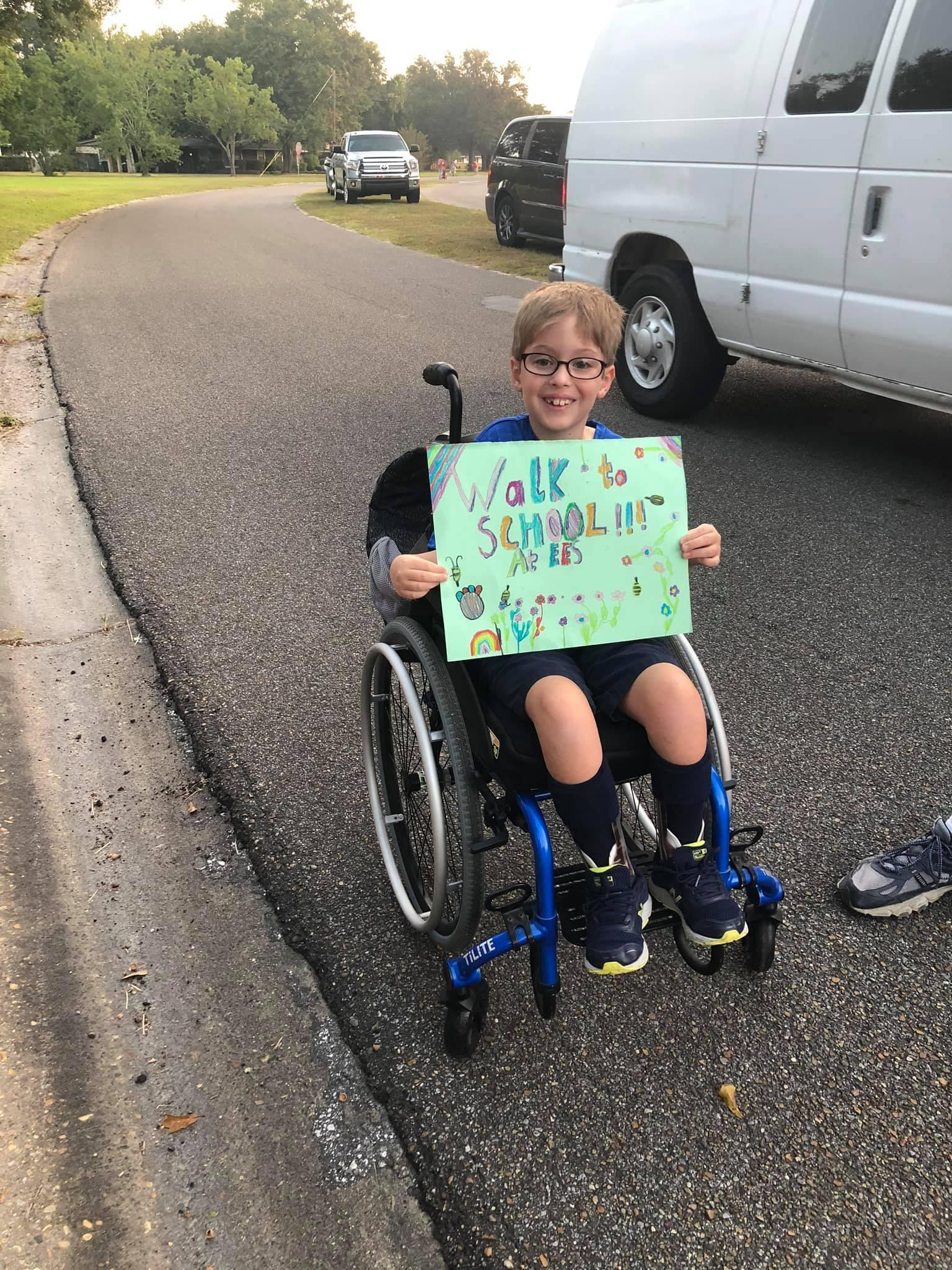 student in wheelchair with sign