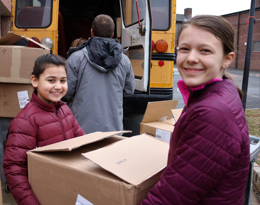 Photo of two Franklin students holding box of toys to be loaded on bus.