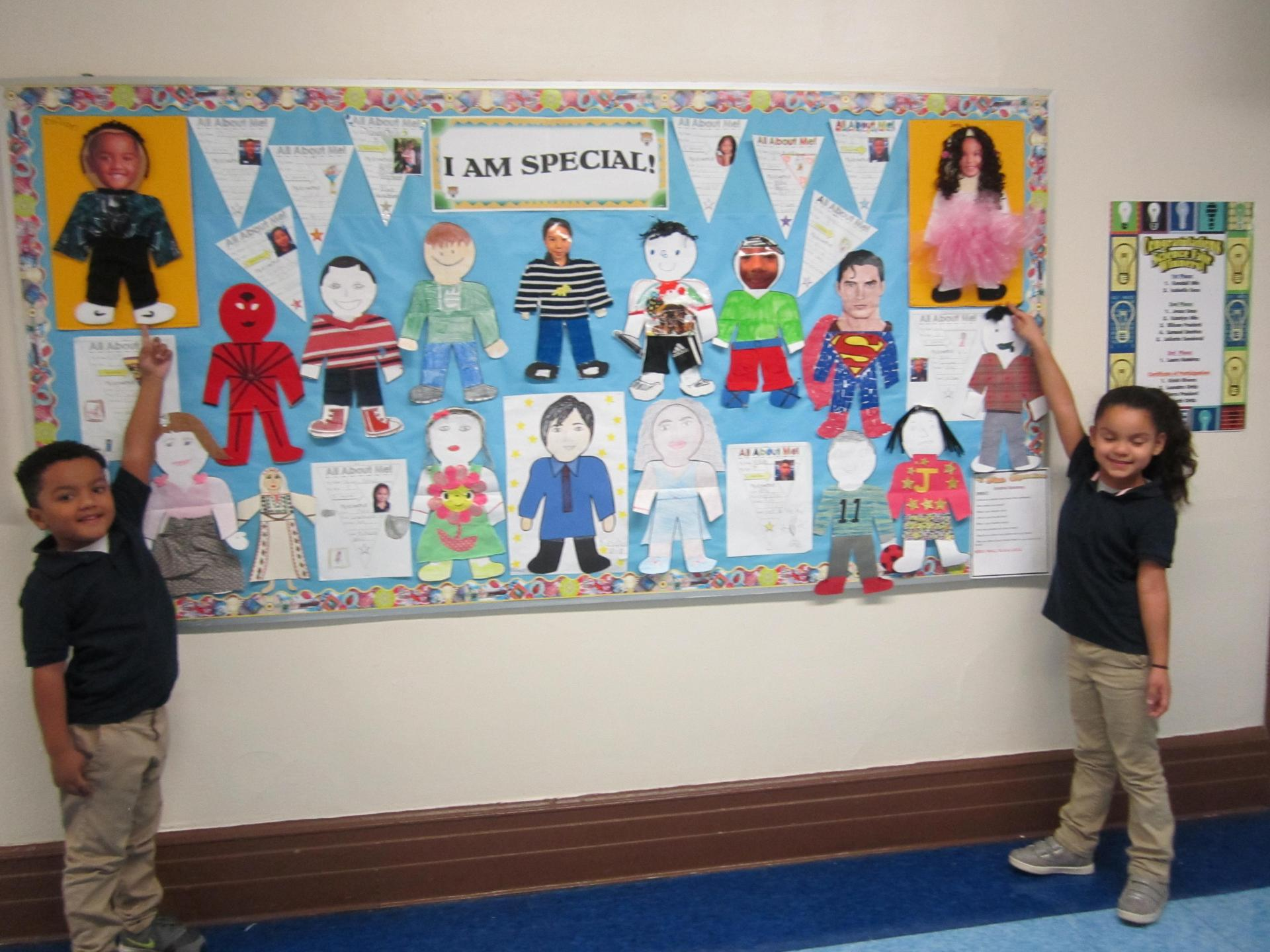 two kids showing off the bulletin board they created