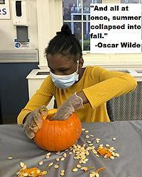 "Residential student preping her Halloween pumpkin. Text:""And all at once, summer collapsed into fall."" -Oscar Wilde"