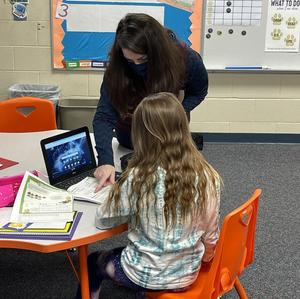 Hybrid support staff member helps a student.