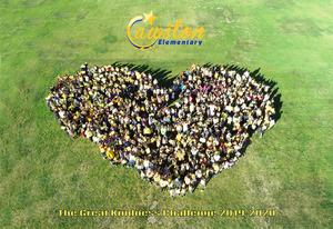 Cawston staff and students on the field in the shape of a heart.