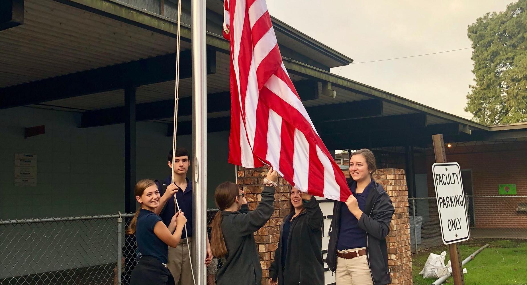students raising the flag