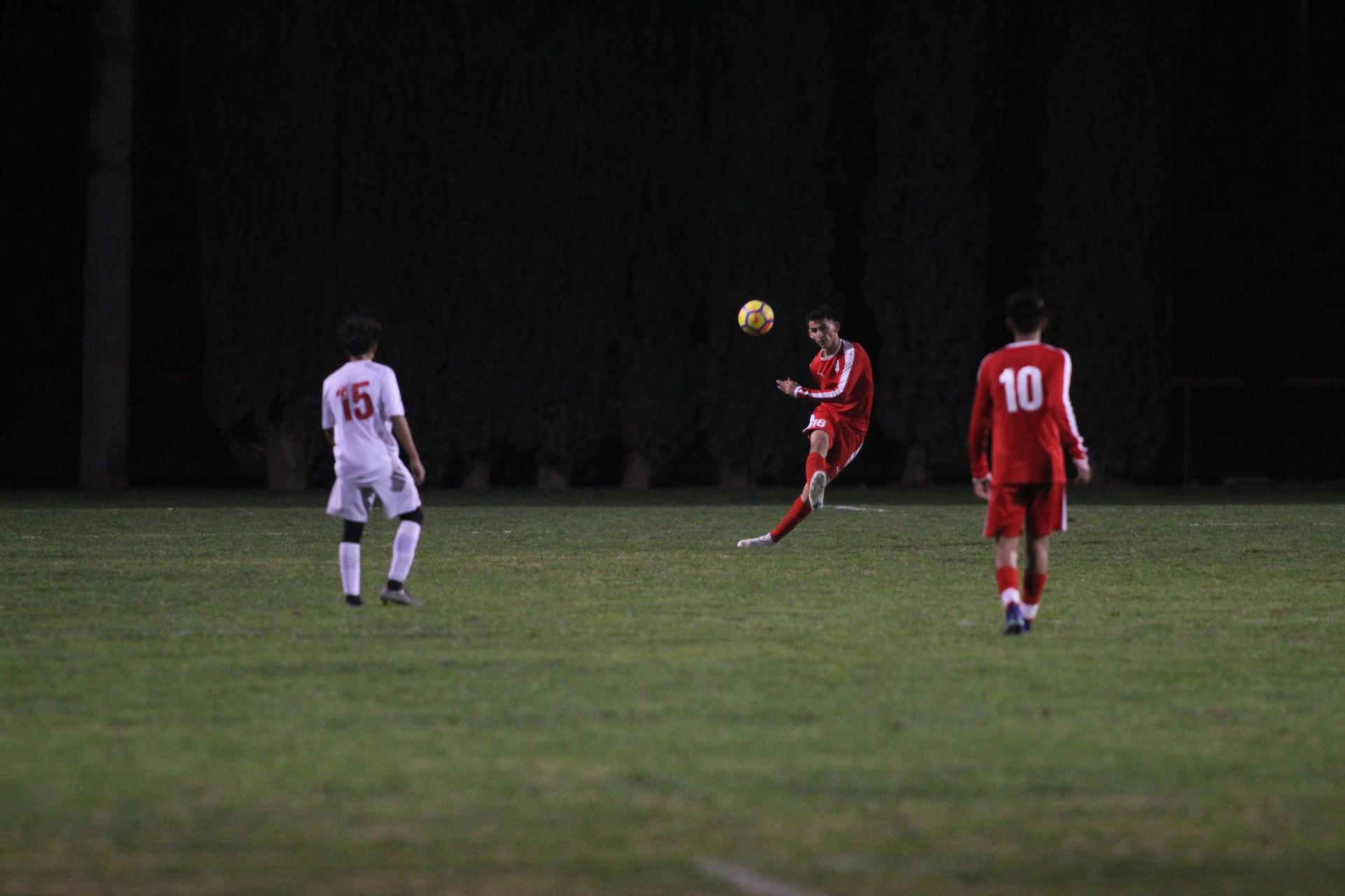 Varsity boys playing soccer against McLane