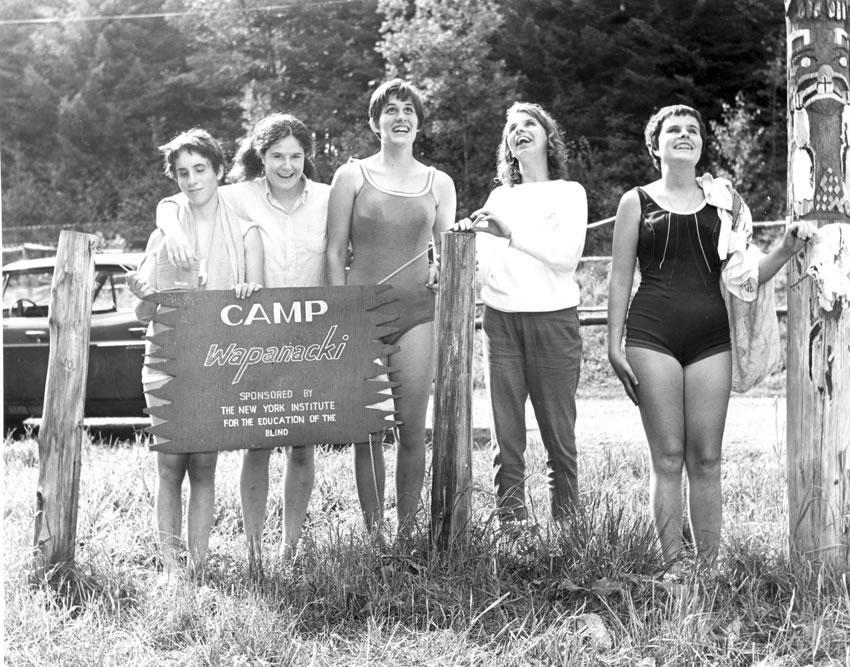A group of female camper at the Camp Wapanaki sign