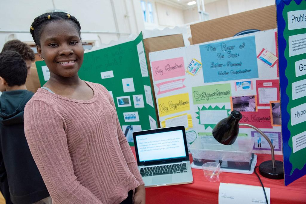 A student stands in front of her science fair project