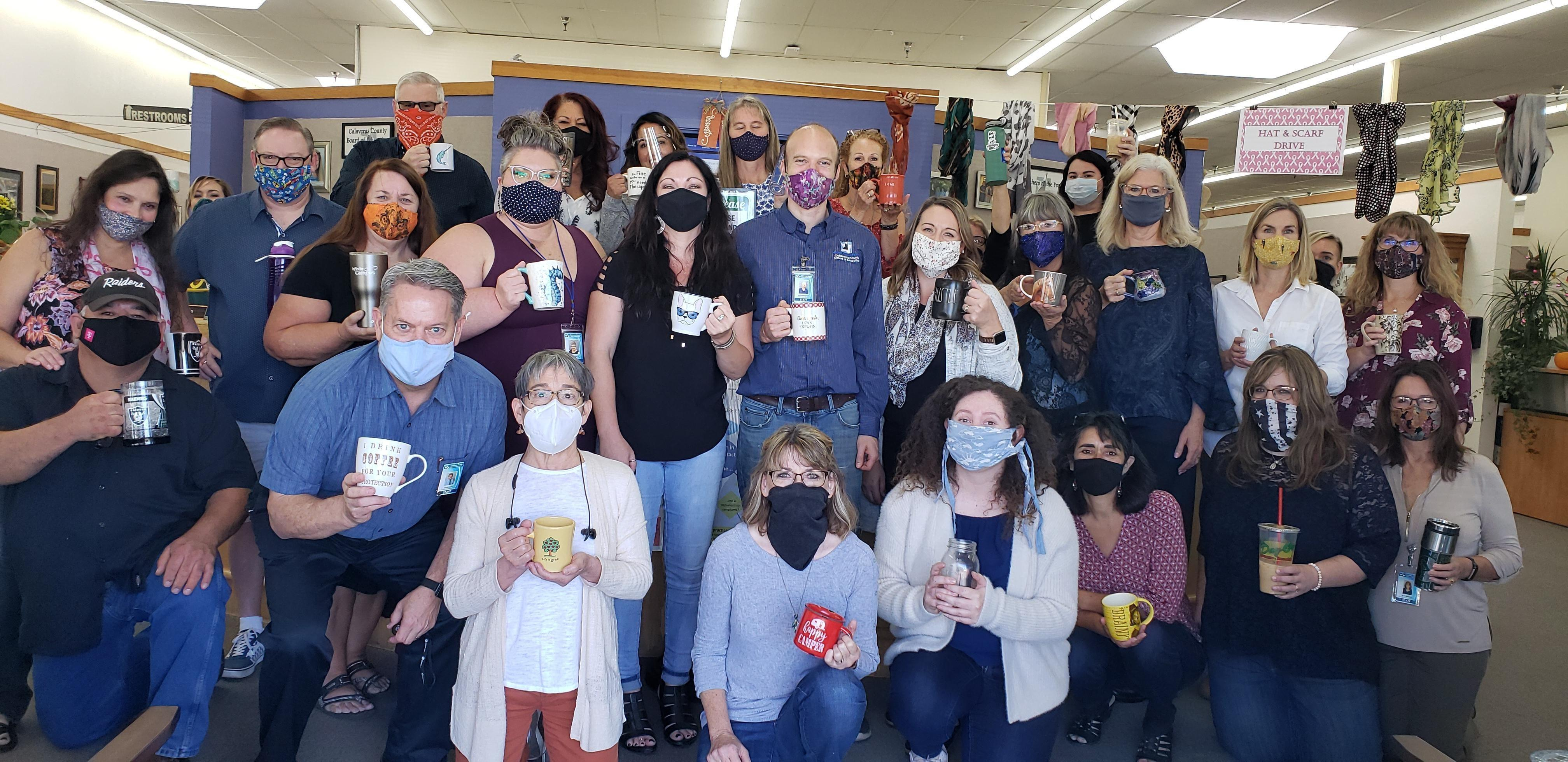 Staff group picture holding mugs wearing masks