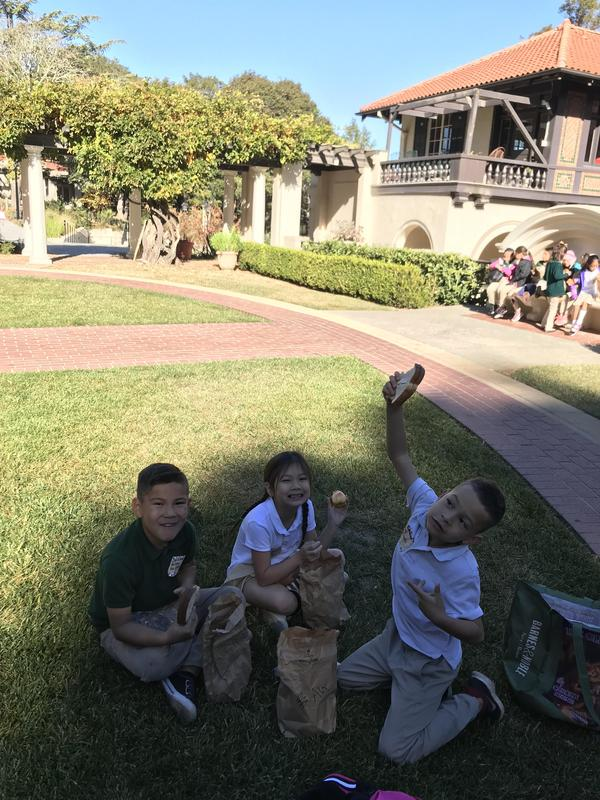 3 kids eating lunch on the grass