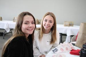 two girls smiling eating lunch