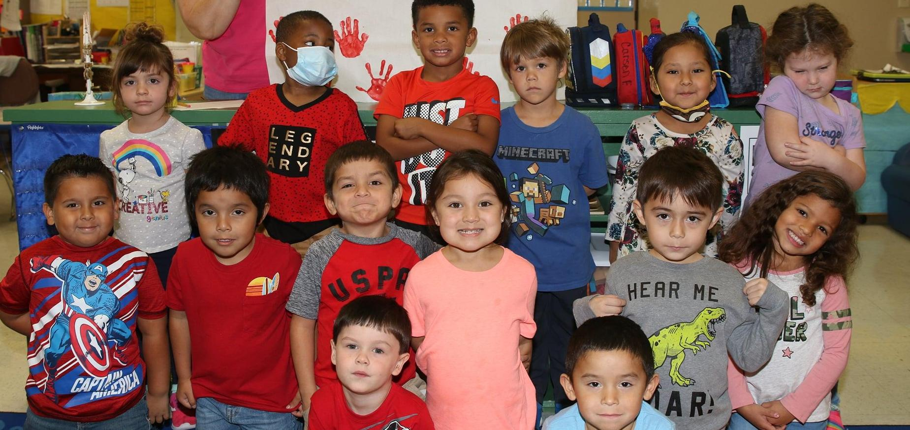PreK students smile for group photo.