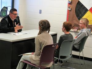 TKHS Principal Tony Petersen conducts a mock job interview with three 7th-grade students.