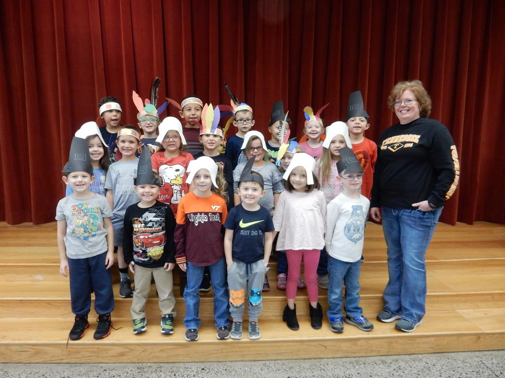 Mrs. Powers' Kindergarten class dressed as Pilgrims and Native Americans posing on the stage for a photo.