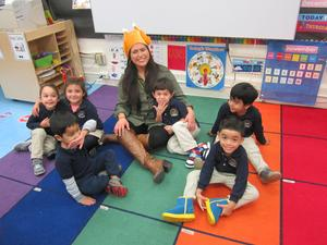 kids on the kiddy rug having fun with their teacher aid wearing a cooked turkey hat