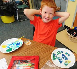 A first grader is all smiles as he finishes painting his ornament.
