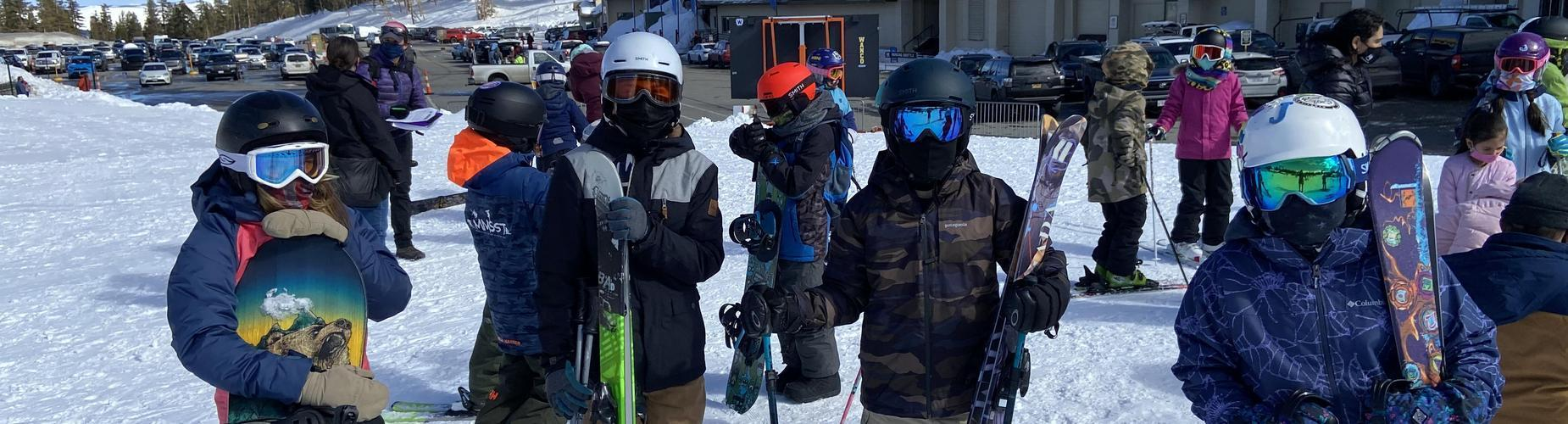 Mes ski pe, students with helmets and googles on the ski slope holding their skis and snowboards.