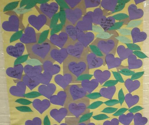 No One Eats Alone Day Poster collage, with student messages on purple and blue hearts.