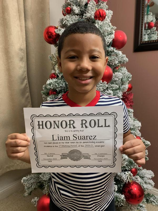 Liam holding honor roll certificate